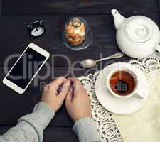 female hands lie on a wooden table, next to a cup of tea and a s