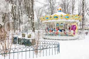 Empty vintage carousel in the park on snowy winter day