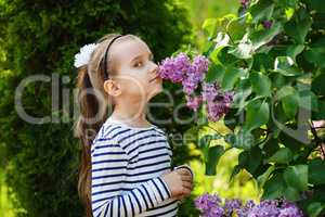 Child smelling lilacs