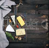cheeses on a brown wooden board: brie, roquefort