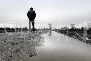 Spaziergänger bei schlechtem Wetter mit Pfütze im Vordergrund