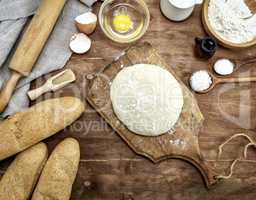 yeast dough made from white wheat on a brown wooden board