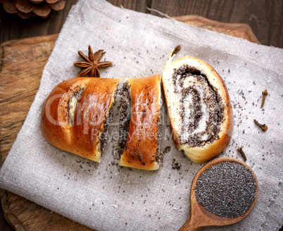 baked roll with poppy seeds on a wooden board