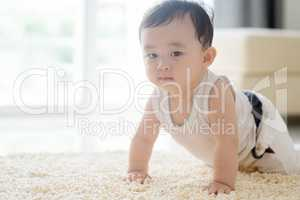 Chinese baby boy crawling on carpet.