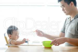 Father feeding baby solid food.