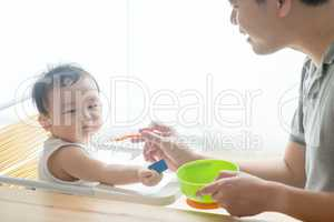 Father feeding toddler solid food.