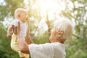 Grandfather playing with grandson outdoors.