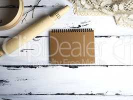 empty paper notepad, wooden rolling pin and a sieve