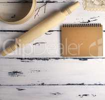 open blank notebook with brown pages and a wooden rolling-pin wi