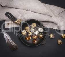 raw quail eggs in a round black cast-iron frying pan