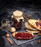 toast of white bread with raspberry jam and a glass jar with jam