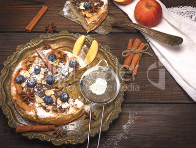 baked round apple pie and iron sieve with powdered sugar
