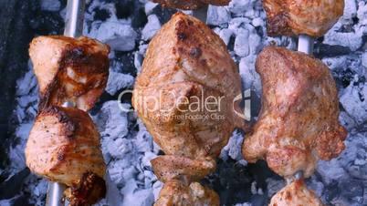 Meat shish kebab preparing on metal skewers in fume