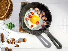 fried chicken egg with pieces of sausage in a black cast-iron fr