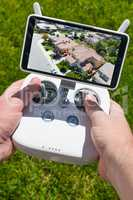 Hands Holding Drone Quadcopter Controller With Residential Homes
