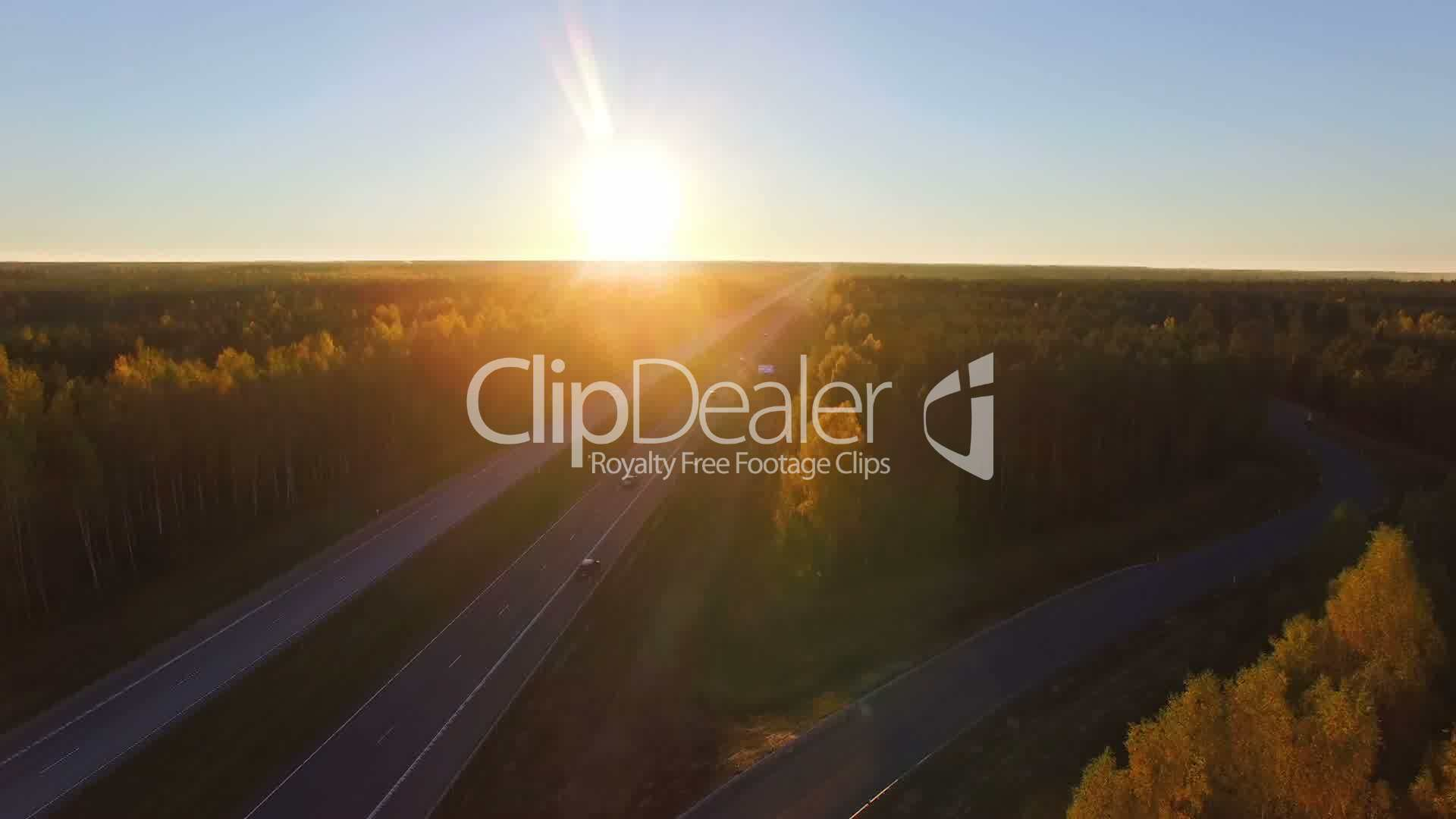 Aerial panoramic of a highway with traffic among a mixed hardwoods