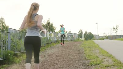 Two girls run along the walkway, meet and have fun talking in the park next to a lake at summer sunset