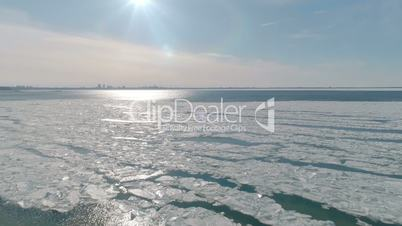 Aerial view of ice on the cold sea with view to the city and with sunlight