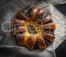 baked round pie with poppy seeds on a gray linen napkin