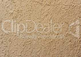 fragment of beige wall with decorative plaster of waves