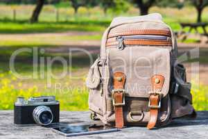 Outfit of traveler,  Different objects on wooden table:  bag, camera, smartphone.