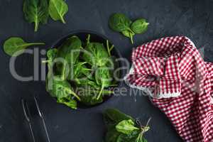 fresh green spinach in a round cast-iron frying pan