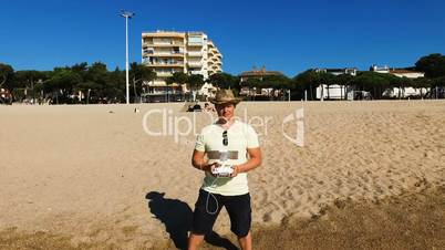 Man controlling drone with transmitter on the coast. Operator makes an areial photo using a drone