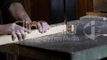 carpenter detail cuts a piece of wood with a band saw