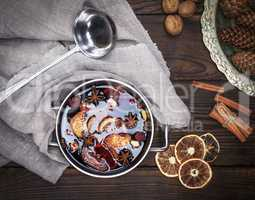 mulled wine with spices and pieces of fruit in a round aluminum