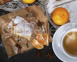 piece of mandarin pie with powdered sugar and white cup of coffe