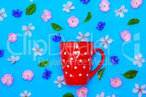 ceramic red mug  with white polka dots on a blue background