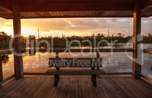 Sunset Wooden bench on a secluded, tranquil boardwalk along a ma