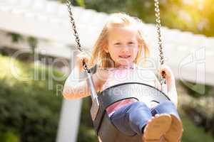 Pretty Young Girl Having Fun On The Swings At The Playground