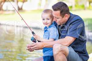 Young Caucasian Father and Son Having Fun Fishing At The Lake