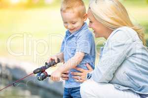 Young Caucasian Mother and Son Having Fun Fishing At The Lake