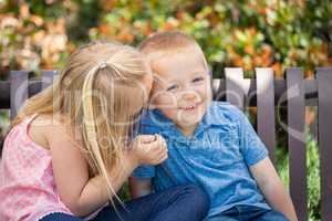 Young Sister and Brother Whispering Secrets On The Bench At The