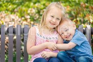 Young Sister and Brother Having Fun On The Bench At The Park