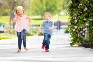 Young Sister and Brother Having Fun Running At The Park