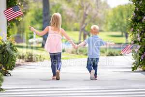 Young Sister and Brother Holding Hands and Waving American Flags