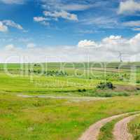 Landscape with hilly field and blue sky.