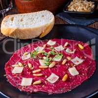 Carpaccio of beef with pine nuts, colorful pepper and Parmesan c