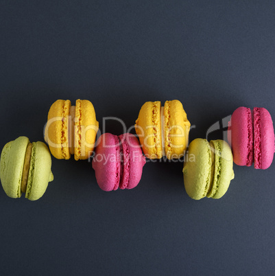 row of multicolored cakes macarons on a black background