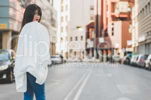 Beautifu young woman with white jacket cross a street