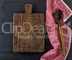 empty old wooden cutting board and a wooden spoon