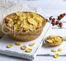 corn flakes in a wooden bowl on a white board
