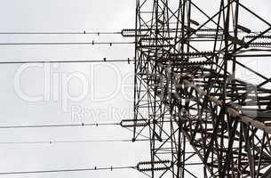 Looking up large electrical tower on overcast day.