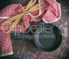round empty black cast-iron frying pan with a red napkin