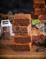 a stack of square pieces of baked brownie