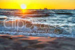 red yellow sunset on the sea shore in the surf of the waves of the Baltic sea and a magnificent sunrise