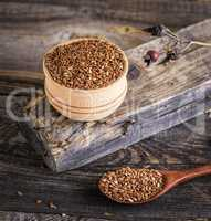 flax seeds in a wooden bowl and spoon